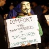 """Protester with Guy Fawkes mask holding sign that reads, """"Comfort the Disturbed + Disturb the Comfortable"""""""