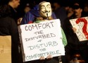 "Protester with Guy Fawkes mask holding sign that reads, ""Comfort the Disturbed + Disturb the Comfortable"""