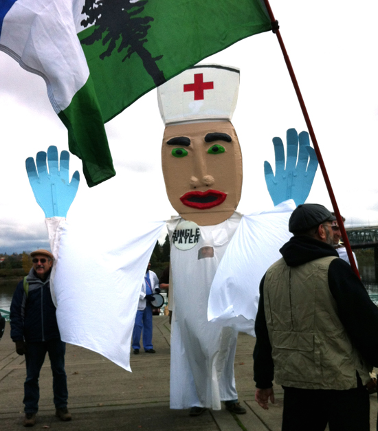 Protesters demonstrating with large nurse puppet (with huge blue hands) for single-payer healthcare