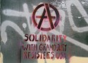 "Stenciled Anarchy ""A"" above the words Solidarity With Grand Jury Resisters, USA"