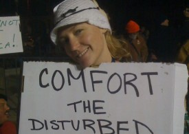 "Kacee Dwyer holds sign that says, ""Comfort the Disturbed"""