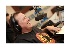 John Kane smiling with headphones on and a microphone in front of him as he does his radio show.