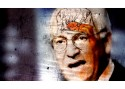 photo of Dick Cheney rendered through a filter making the image look aged and crack. Superimposed on his forehead to look like the shape of his brain inside, is a drawing of two figures waterboarding a third figure in an orange jumpsuit
