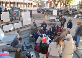 Occupy Tucson circa Winter 2011-2012: group of about 30 meeting around a table in the dried up pond at Veinte de Agosto park with onlookers.