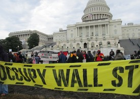 "Occupy Congress protestors on January 17, 2012 hold a large yellow banner with black stencil-stylized text ""OCCUPY WALL ST"""