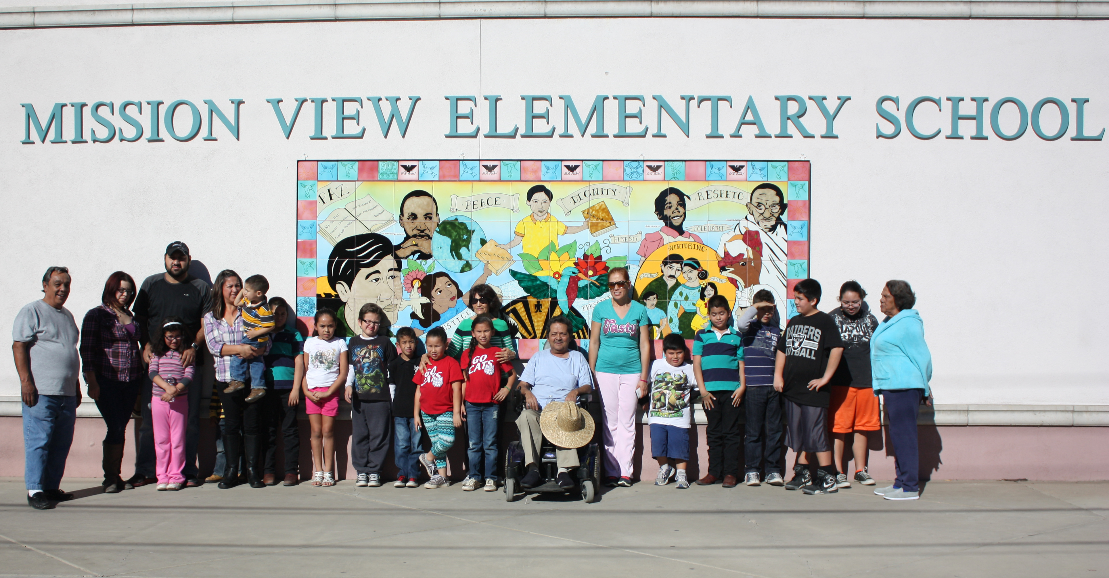 photo of concerned families in South Tucson standing in front of Mission View Elementary School with school name and mural behind them (22 people, 14 of them children)