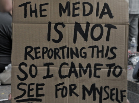 """Man holding a sign that reads, """"The media is not reporting this so I came to see for myself."""""""