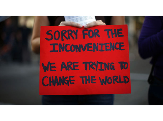 """Zoom-in of sign held by protester. Reads, """"Sorry for the inconvenience. We are trying to change the world."""""""