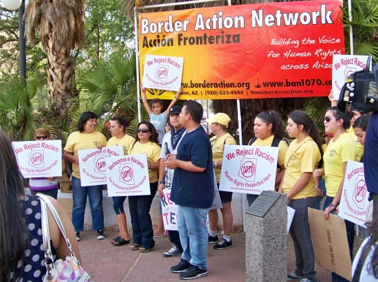 Protesters gather outside the Arizona State Building holding signs rejecting SB 1070