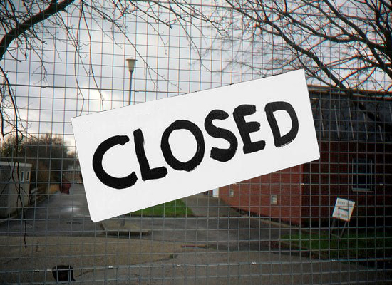 """Empty school in background, fence with large """"CLOSED"""" sign in foreground"""