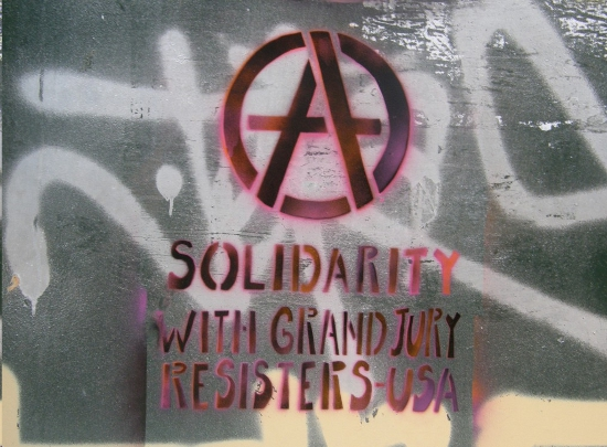 """Stenciled Anarchy """"A"""" above the words Solidarity With Grand Jury Resisters, USA"""