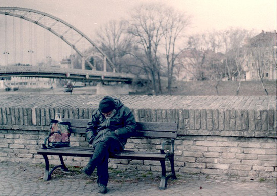 photograph of homeless man sitting on bench, the image has been manipulated so that the man's surroundings are sepia-toned to emphasize the focus on him.