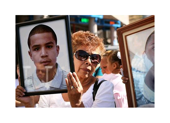 Photo of Taide Elena holding up a picture of her grandson Jose Antonio Elena Rodriguez