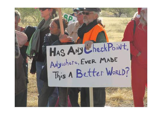 """Protesters holding signs, one in particular is featured that reads, """"Has Any Check Point, Anywhere, Ever Made This A Better World?"""""""