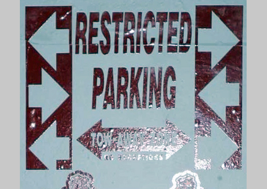 "Sign in Tucson marking a ""Tow Away Zone"" and ""Restricted Parking"""