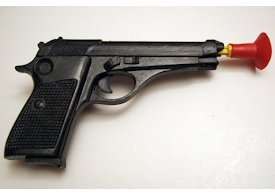 Black toy pistol with large red suction cup on white background
