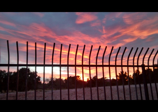 Picture at sunset of the bars of the fence at the El Rio Golf Course
