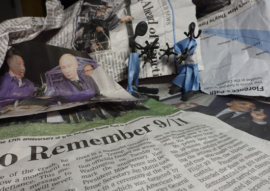 Photograph of two toy figures standing among some crumpled up newspapers...
