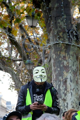Picture of Paris demonstrator in a yellow vest, wearing a Guy Fawkes mask
